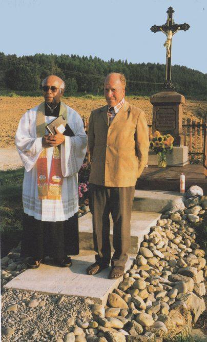 Mann mit einem Pfarrer vor einem Feldkreuz