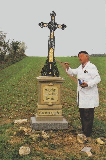 Mann bemalt ein Feldkreuz