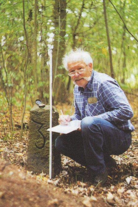 Mann kniet vor einem Grenzstein im Wald
