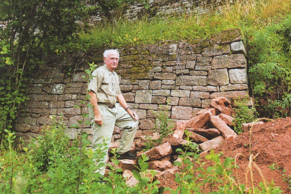 Mann vor einer Mauer