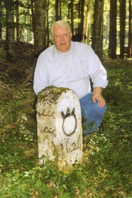Mann kniet an einem Grenzstein im Wald