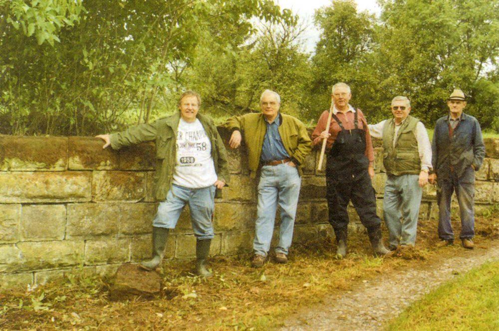 fünf Männer an einer Mauer