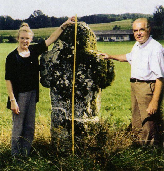 Mann und Frau an einem steinernen Kreuz auf einer Wiese