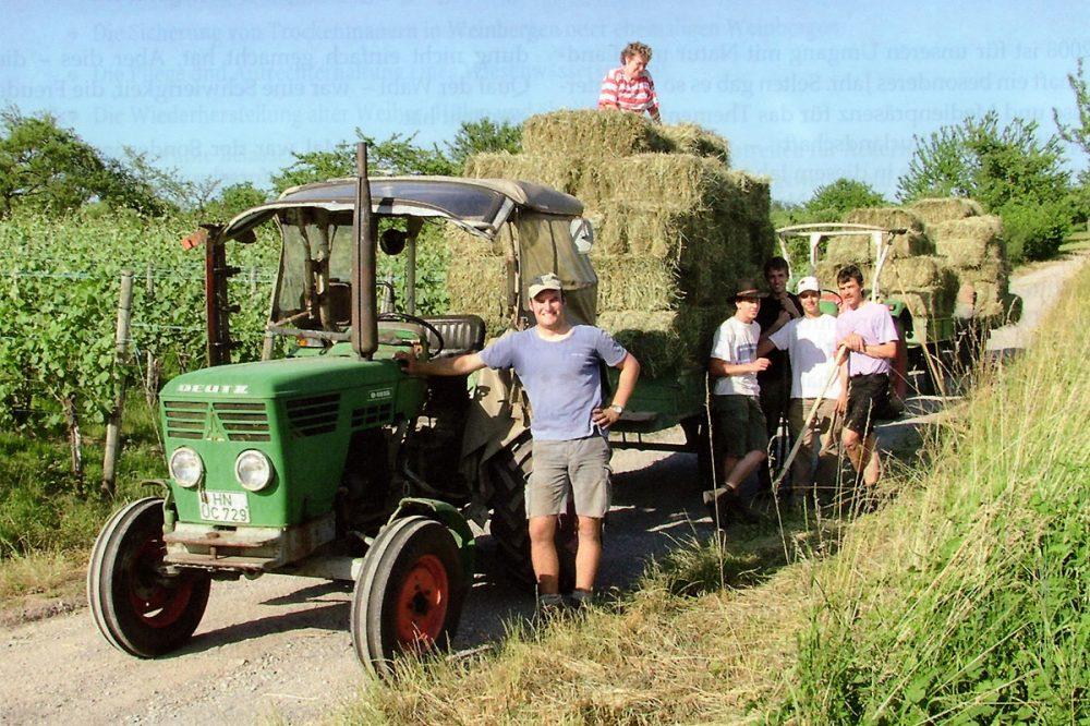 Menschen an einem Traktor mit beladenen Anhängern