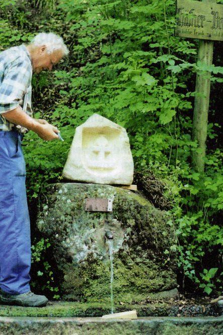 Mann an einem Brunnen im Wald