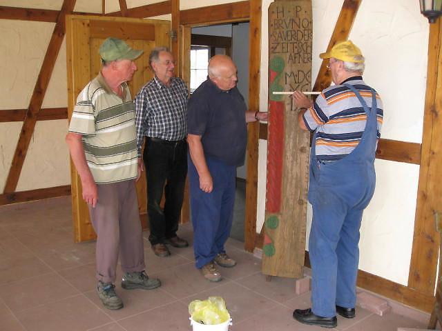 vier Männer betrachten ein historisches hölzernes Bauteil eines Hauses