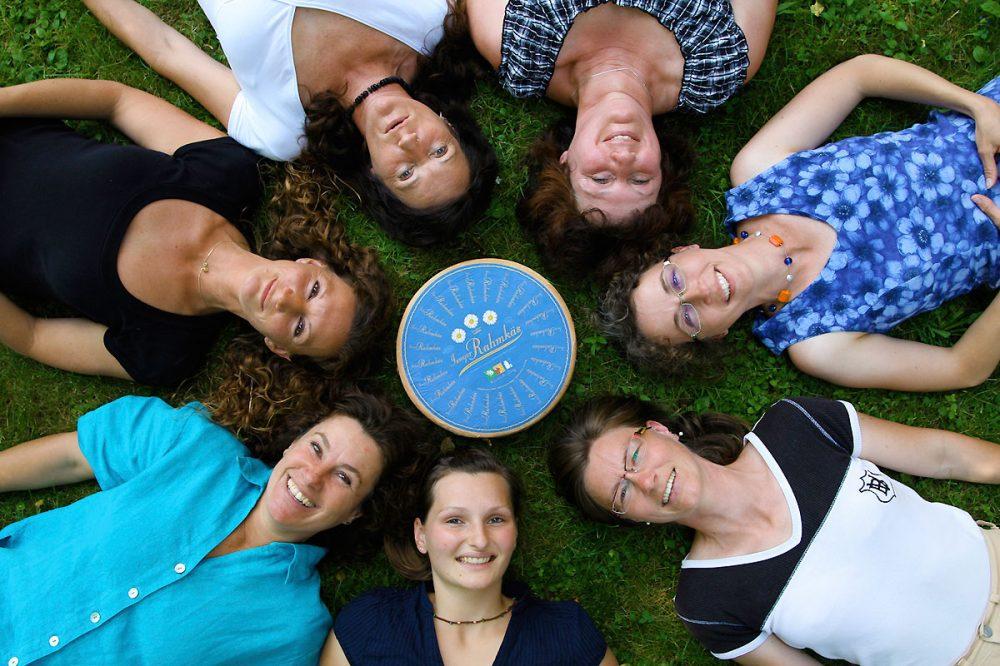 sieben Frauen liegen im Gras um einen großen Käselaib herum