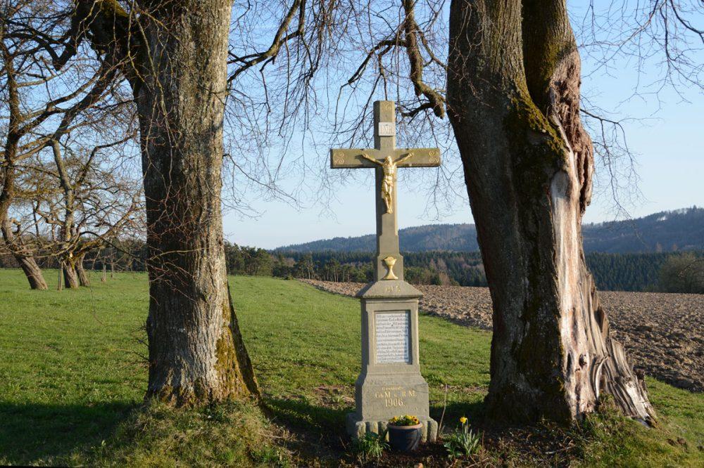 Feldkreuz zwischen zwei großen Bäumen