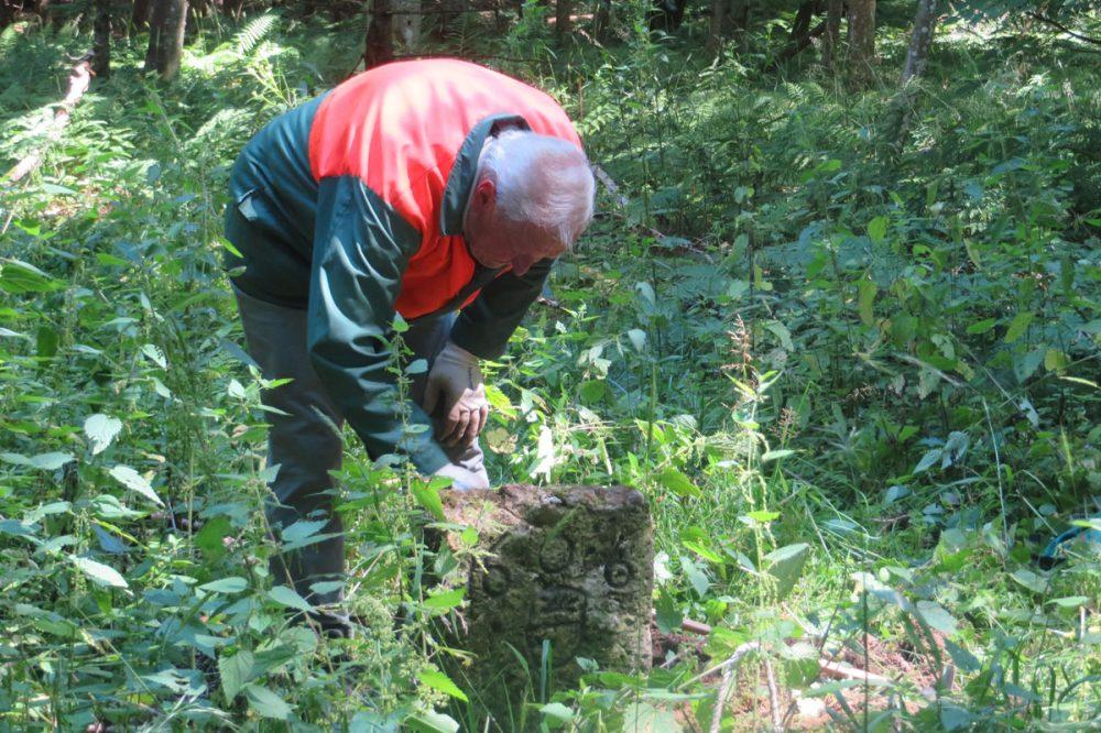 Mann an einem Grenzstein im Wald