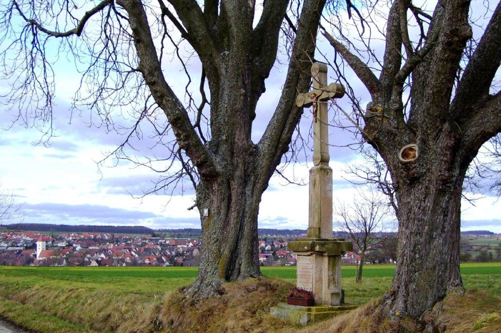 Feldkreuz zwischen zwei Bäumen