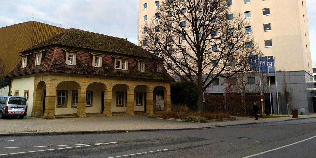 kleines historisches Gebäude neben großem Hotelhochhaus