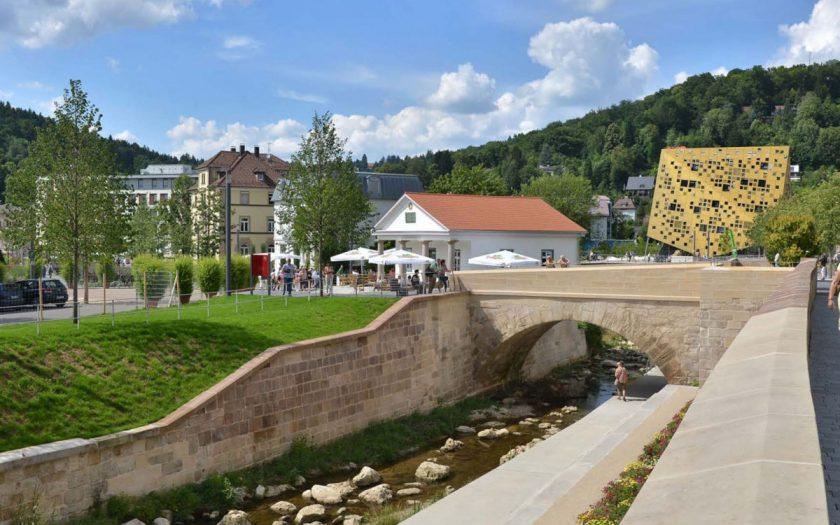 Brücke über einen Bach vor einem historischen Gebäude